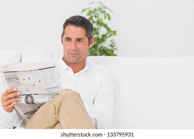 Serious man reading a news paper in the living room