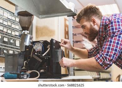 Serious man repairing broken coffee machine