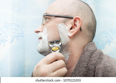 Serious man shaving his beard by razor blade. Side view