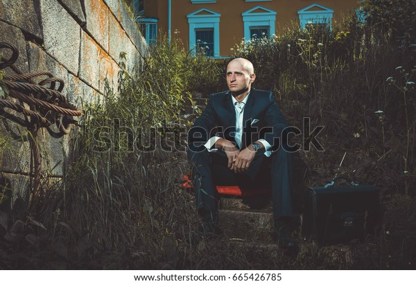Serious man sitting on a old broken stairs