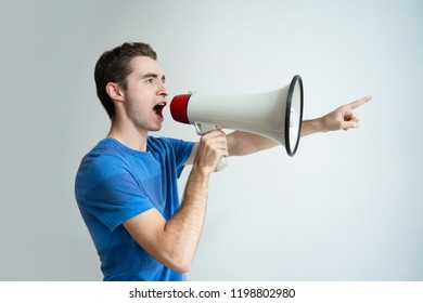 Serious man speaking into megaphone and pointing away. Young guy looking away. Promotion concept. Isolated side view on white background.
