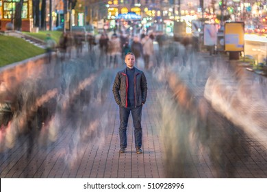 The serious man stand in the ghost-like crowd stream. Evening - night time, warm color