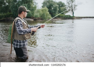 Serious man is standing in water and fishing. He has spinning in hands and fishing net on the back. Guy wears vest, waders, shirt and cap.
