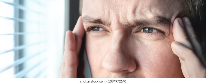 Serious man with stress. Ashamed or depressed person. Burnout, amnesia, memory loss or ptsd concept. Migraine or headache. Candid close up of guy rubbing head and touching temples by the window.