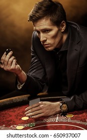 Serious man in suit holding playing cards and poker chip in casino