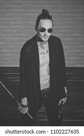 Serious man. Man with swords standing on wooden floor, top view. Harakiri, suicide ritual. Samurai, buddhist concept. Warrior in black sunglasses and open clothes showing tattooed torso. Honor and