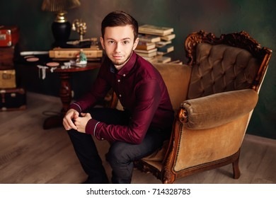 Serious man in vintage hotel sitting in lobby and looking at camera