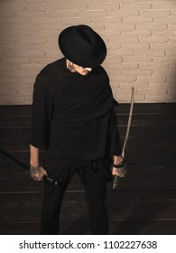 Serious man. Warrior in black hat and clothes, top view. Man with swords standing on wooden floor. Samurai, buddhist concept. Honor and dignity. Harakiri, suicide ritual.