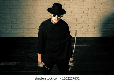 Serious man. Warrior in black sunglasses, hat and clothes, top view. Man with swords standing on wooden floor. Honor and dignity. Samurai, buddhist concept. Harakiri, suicide ritual.