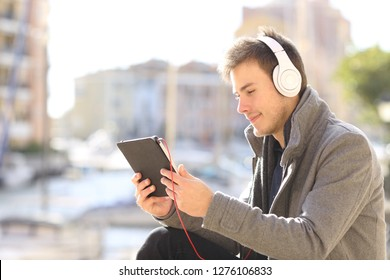 Serious man watching and listening media on a tablet sitting in the street of a coast town