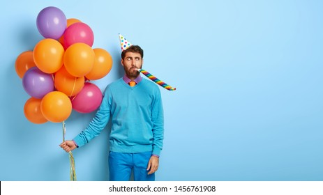 Serious man wears cone birthday hat, blows in party whistle, holds colorful air balloons, dressed in neat blue clothes, stands indoor, celebrates anniversary. Blank copy space for your information