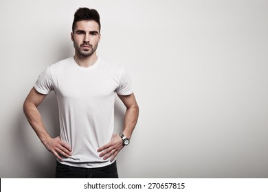 Serious man in white blank t-shirt, white wall background