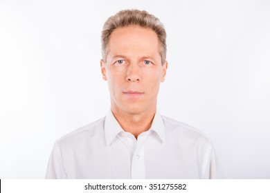 Serious man in a white shirt standing on the white background