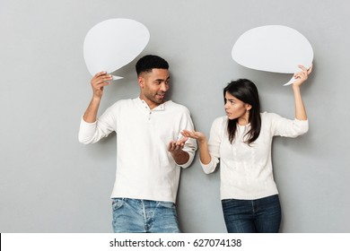 Serious man and woman talking and holding blank bubbles isolated