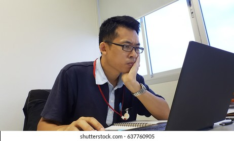 A serious man working in front of the laptop computer