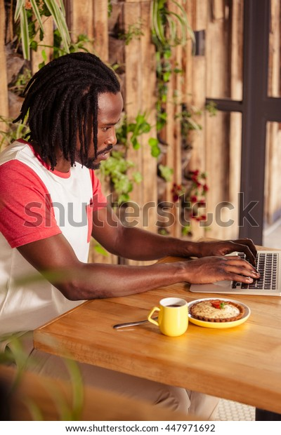Serious man working on laptop at coffee shop