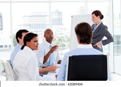 Serious manager giving presentation to her team in the office