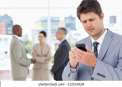 Serious manager sending a text with his mobile phone