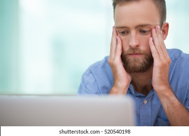 Serious manager sitting at laptop in stress