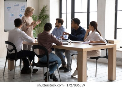 Serious mature 60 year old businesswoman flip charts presentation with financial charts in boardroom at company meeting. Confident adult auditor speaks with diverse colleagues about project.