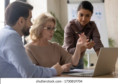 Serious mature 60 year old businesswoman using laptop with young indian female and businessman mentor signing contract in office at meeting. Confident diverse woman managers talking about new business