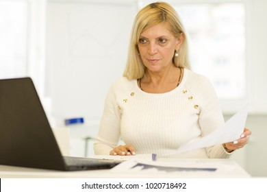 Serious mature beautiful businesswoman working at her office using laptop looking concentrated copyspace technology professionalism confidence achieving career executive entrepreneur.