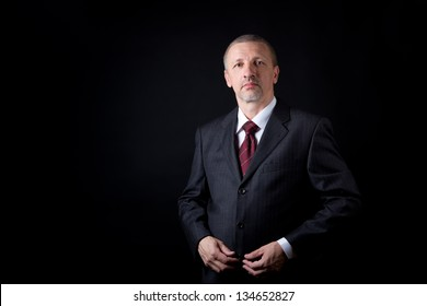 Serious mature businessman looking at camera. Black background