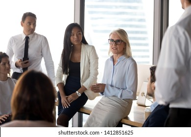 Serious mature businesswoman hold informal team meeting in conference room, discuss ideas or plans, focused middle-aged female CEO speak at group company briefing brainstorming together in office