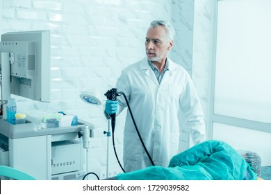 Serious mature doctor holding a modern endoscope and preparing for the procedure