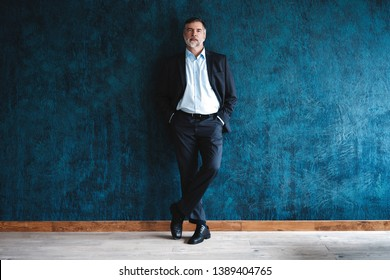 Serious mature man posing in front of a dark blue background with copy space