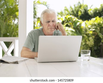 Serious mature man using laptop at verandah table
