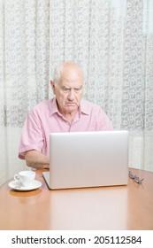 Serious mature man using laptop at table
