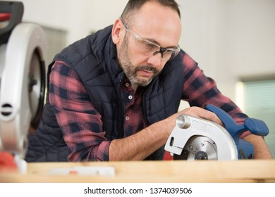 serious mature man working in carpentry workshop