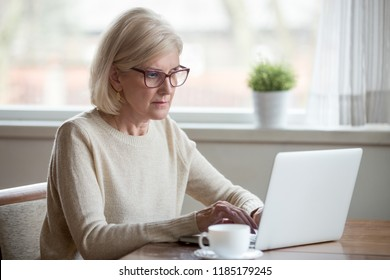 Serious mature middle aged business woman in glasses using laptop typing email working at home office, thoughtful focused senior old lady searching information on internet or communicating online