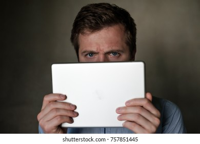 Serious mature middle aged man looking into tablet and frown his face. He is angry with information he just received