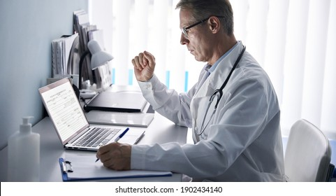 Serious mature old doctor physician using laptop tech in hospital office. Senior middle aged male gp checking patient clinical registration form, elearning working looking at computer sitting at desk.