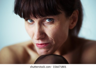 serious mature woman with bared shoulders looking at camera