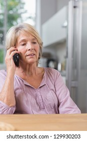 Serious mature woman calling in the kitchen