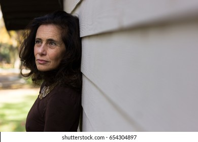 Serious mature woman on brown sweater and necklace leaning against white wooden plank wall. Middle aged classy lady with concerned, worried look. Retirement, menopause, problem concepts