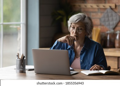 Serious mature woman wearing glasses working on laptop online, sitting at desk on kitchen, focused senior businesswoman reading email, looking at screen, watching webinar, studying in internet