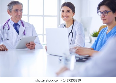 Serious medical team discussing patient's case in a bright office