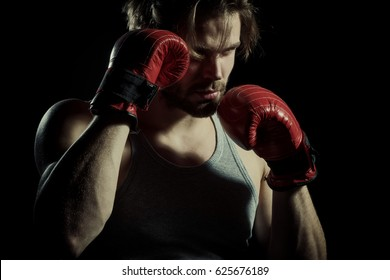 Serious men in boxing gloves are practicing. Cool young man with boxing gloves. Attractive guy boxer closeup on black background