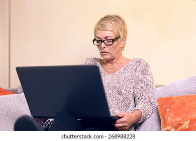 Serious Middle Age Woman with Short Blond Hair Sitting on Sofa While Using her Laptop Computer.