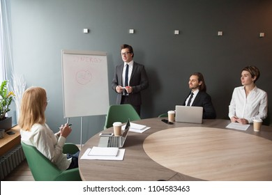Serious middle aged businessman presenting company business goals to colleagues during meeting in boardroom, male coach training workers, explaining successful strategies on flipchart during briefing