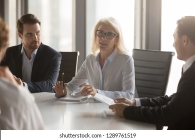 Serious middle aged businesswoman talks at group board executive meeting, confident mature old female leader speaking discussing work offers solution negotiating with partners at corporate briefing