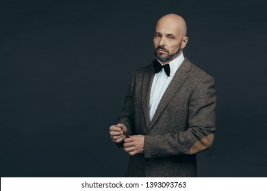 Serious middle aged man with a deadpan face expression dressed in casual posing on a dark gray background with copy space
