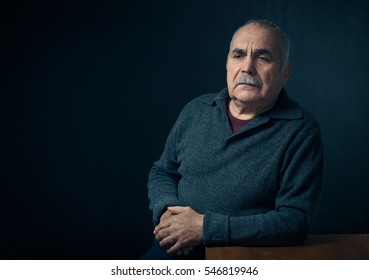Serious middle aged man with mustache and jumper leaning on table, copy space in background