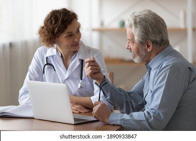 Serious middle aged retired man consulting with young female physician doctor at checkup meeting in hospital. Skilled general practitioner giving healthcare medical advices to mature patient.