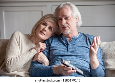 Serious middle aged senior couple embracing talking watching tv together at home, retired mature older family talking discussing television news with remote control sitting on sofa in living room