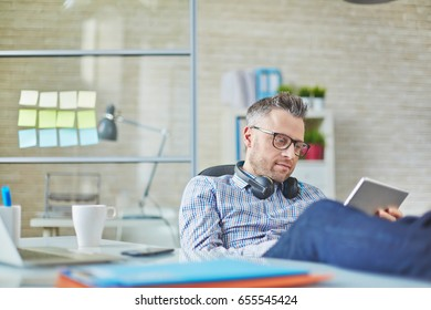 Serious middle-aged businessman wearing headphones analyzing data on tablet when he working alone in office